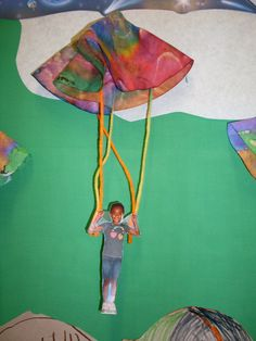 For my transportation interactive bulletin board my students created parachutes.  Use coffee filters decorated with watercolors, bingo markers or markers sprayed down with water.  Take a picture of each child with their arms up as if holding on parachute lines. Attached the parachute with yarn or string with tape to the picture.  The parachutes will float down if you weigh them on the bottom with paperclips.  Both the students and parents love them.  Fun and super easy to make.
