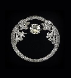 ART DECO DIAMOND PLATINUM ORNAMENTAL CIRCLE BROOCH.