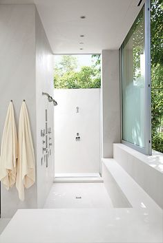 Views of a master bath in Los Angeles, a collaboration between Lehrer Architects and Unique Custom Interiors: The indoor/outdoor shower, surfaced in honed limestone and marble, features Hansgrohe heads, Dornbracht controls, and Kohler WaterTile sprayers.