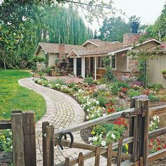 A beautiful garden and curved stone path dress up this home's entry. See more front yard flower gardens: http://www.bhg.com/gardening/landscaping-projects/landscape-basics/front-yard-flower-power/?socsrc=bhgpin080812frontyardgardenpath