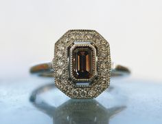 Cognac diamond halo Handmade recycled platinum ring. Detached halo style with a central Argyle cognac emerald cut diamond in a milgrained bezel centre and white Argyle diamonds bead set in the milgrain edged halo. The ring has a plain polished band.