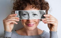 Young woman with curly brown hair holding picture of older woman's aged eyes over her own. Old vs young, youth vs aged