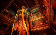 The Giant Buddha. This thing was a pleasure to photograph! While I was in this temple, monks were taking huge long red sashes and walking around the upper areas and draping them around different parts of the enormous statue. It was all in slow motion and most interesting! - Trey Ratcliff