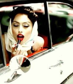 Vintage styled modern pinup girl in retro car with lipstick