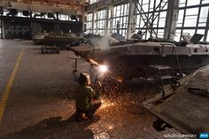 UKRAINE, ZHYTOMYR: A worker welds the body of an armoured personnel carrier (APC) during repair work in a tank plant in Zhytomyr, some 150km west of Kiev, on July 10, 2014. The workers and employees of the plant repair armored vehicles and tanks which were used by Ukrainian governmen forces during the assault on pro-Russian insurgents in the east of the country. Ukraine warned on July 9 that its assault on pro-Russian insurgents may last another month and rejected calls for a ...