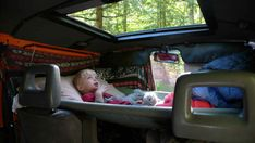 Zen Adventure Van Modifications - Bed (choosing this picture because it's awesome that this little one has a way to watch for shooting stars,.. But pinning because there are several ideas on this one for adding sleeping/storage to a van)