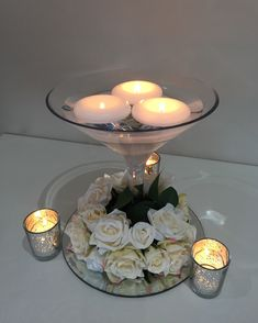 Cocktail vase centrepiece with floating candles and ivory rose trim at the base, accompanies by silver tea lights #piecesandposies