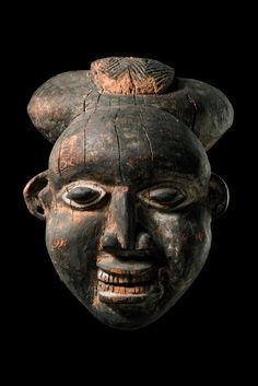 Helmet mask.  Cameroon, Tikar.  Present mask probably typifies the stoic, non-committal expression of the faithful household servant. Application of white chalk around eyes, ears, and the mouth identify the bearer as a carrier of bad news.