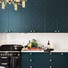Bottle Green kitchen in Big Fish pattern. If fish ain't your thing, you can always turn these fronts upside down, like the owner of this apartment did. Handles are the solid brass Balls handles, flirting with the Swedish, classic Hans-Agne Jakobsson chandelier in brass and smoke coloured glass from 1959. Have a great Friday everyone! Photographer: Adam Helbaloui @kronfoto and styling by @myricastylist.
