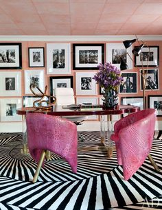Raspberry leather chairs by Wearstler bring color to the wife's office, where a collection of photos is displayed; the tube sculpture on the desk is also by Wearstler, and the carpet was custom made by the Rug Company.