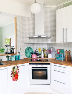 Look at the amazing space this corner stove/oven combination creates. I LOVE the space behind the stove for displaying pretty things - or even propping up your cook book! Peter Carlsson via House of Turquoise