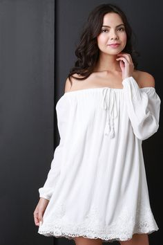 Description This off-the-shoulder peasant dress features an elasticized ruffled neckline with a non adjustable tassel tie, long sleeves with elasticized cuffs.Finished with a relaxed fit and crochet d