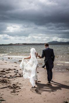 Bride and groom walking on the beach on their wedding day. Weddings in Ireland, Weddings by Tara & Dave, Destination Weddings.