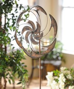 Put a new spin on your garden décor with this Antiqued Metal Wind Spinner! The bronze finish and the teal rust accents make this pinwheel look like a true antique. #kirklands #SpringisintheAir