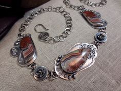 "With its curling scrollwork, full-blown roses, dots, and scalloped edges, this piece looks like a Victorian valentine.  Not to mention the lacy bands of color in the stones themselves.  Red, the color of love, this one is romantic to its core.  Makes me want to sing "" I Feel Pretty"" when I put it on.    All silver components were handcrafted by me from solid sterling silver sheet and wire except for the chain, which is made of fine silver (99.9% silver) fused links.  All sawing, filing, ..."