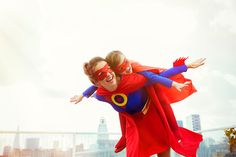 Stock Photo : Superhero mother and daughter playing on city rooftop