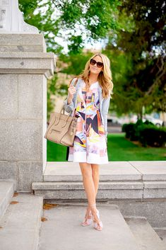 Emily Jackson Is Wearing Patterned Dress From Clover Canyon, Denim Jacket From J. Brand, Shoes From Alexander Wang, Sunglasses From Prada And The Bag Is From Celine