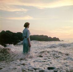 Rückenansicht einer Frau am Meer: Ihre Beine von der Brandung umspült. Die...