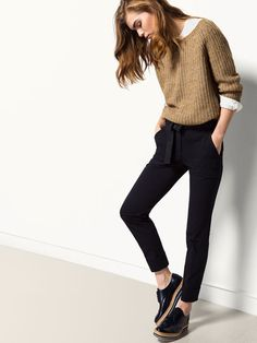 White shirt, olive green sweater, black pants, black shoes