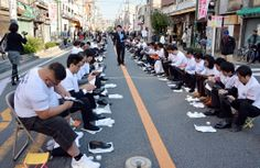 Some 800 participants polish their leather shoes on a street in Tokyo's Taito ward, a district famous for its shoemakers in Japan, to challe...