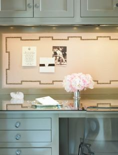 Glass top wall desk, and cushioned nailhead bulletin board on wall.