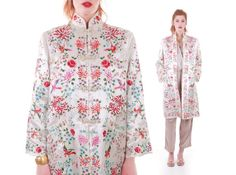 Vintage embroidered silk jacket.  Intricately detailed and colorful birds and blossoms.  Medium weight, high quality ivory off white silk satin.  Mandarin collar.  Darts at bust.  Four satin frog toggle closures.  Two angled welt pockets in front.  Squared, sturdy fabric interfacing in shoulders.  An unusual construction feature that could date this earlier than 1960.  Fully lined in thin, semi sheer off white silk.  Below hip length.  Slight A - line silhouette.  Inc...