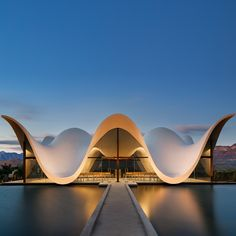 A bright white canopy undulates above the glazed walls of this chapel outside Cape Town, framing views right through it to scenic mountains, vineyards and pomegranate orchards.