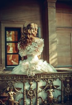 He saw her standing there on the balcony dressed more beautifully than ever. But her face was distant and sorrowful. It pained John to think of her.