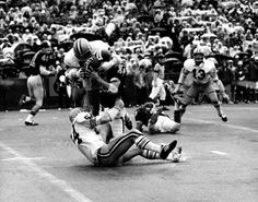 Black and white photo of University of Oregon linebacker Bill Meyer (#54) pulling an opposing quarterback to the ground with the help of an unidentified defender while safety Greg Brosterhous (#13) watches from his pass defense assignment during a game played at Autzen Stadium in 1972. ©University of Oregon Libraries - Special Collections and University Archives