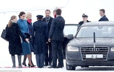 The royals were given a warm welcome to Norway as they touched down in snow Oslo - with Kate and Mette-Marit's choice of footwear proving rather less practical than one of the airport officials who wore sensible snow boots (far left)