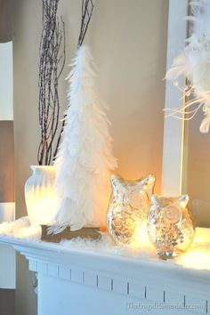 Winter White Mantel with white feather tree, mercury glass owls, rustic branches, and soft, warm lighting.