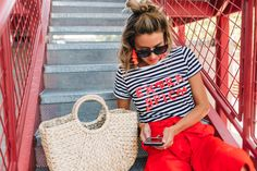 3 easy tricks fashion bloggers like Christine Andrew from Hello Fashion use to put together cute 2017 summer outfits daily, how to layer, pick a color palette, the 3rd piece, how to accessorize and how to pick wardrobe accent colors, red outfit, striped tee, red stripes, pom pom sandals, straw bag, wide leg pants, culottes, tassel earring, french style