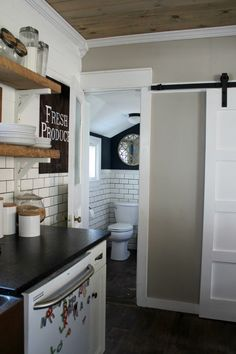 Incredible small bathroom makeover off of the most beautiful farmhouse kitchen. This view used to look TERRIBLE before - and you have to get a look at it now!