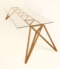 """Strala is known for their line of limited edition objects but this year they're mixing it up with their """"cult object"""" line of unlimited pieces. The Ponte table is the first such design and it's a good one. The angular wood frame is made of solid oak and stands out under the glass tabletop. The sharply angled legs are to hold the weight of the glass but aesthetically they really make the table."""
