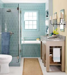 Watery Blue + Taupe + Buttery Yellow Shimmering blue tiles forming the tub and shower surround in this bathroom instantly convey a tranquil, spa-like energy. The taupe hue on the narrow vanity complements the tilework, as does the buttery yellow wall behind the vanity./