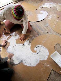 Fissate lo stencil per decorare il pavimento con dell'adesivo e poi passate la vernice