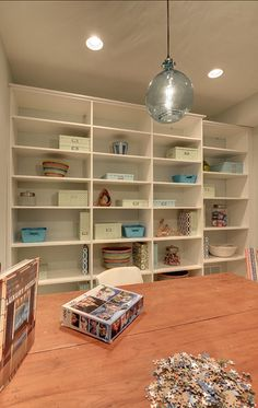 I think this would be the idea, eventually- one whole wall covered with white shelving.