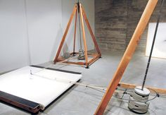 two nine-foot towers use the weight of pendulums to create large-scale spirograph images, in a machine that echoes the designs and interests of the renaissance period and 19th century harmonographs.
