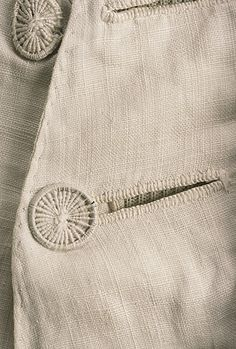 """Detail buttons, waistcoat, probably England, Plain weave bleached white linen, quilted to shape with intricately corded designs, """"French closure"""" with wire and thread-work buttons, linen lining."""