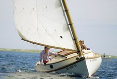This is a gaff-rigged cat boat, attributed to Cape Cod, but rare nearly everywhere, now. These beamy (wide) boats with a single mast and large sail forward, near the bow, are comfortable and simple to sail.  The clean decks leave space for relaxing and much room for brightwork and other nice touches.
