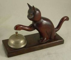 Connecticut, 1930s - Vintage Folk Art ~ HOTEL COUNTER BELL in the shape of a cat. Here's a very unusual front desk/hotel bell. While the bell is metal, the cat is mahogany wood, clearly hand carved w/ lovely glass eyes. You push down on the cat's tail & the paw dings the bell | $270