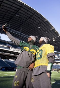 Edmonton Eskimos Willie Jefferson (99) and quarterback Mike Reilly (13) take a selfie during a team practice on Nov. 28, 2015 in Winnipeg. The Eskimos will play the Ottawa Redblacks in the 103rd Grey Cup Sunday.   Photo by Greg Southam, Edmonton Journal