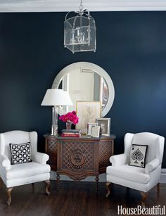 An entry wall in Ralph Lauren's Bone Black sets off vintage chairs upholstered in the simple white cotton Fulk used throughout the house. Jonathan Adler pillows.