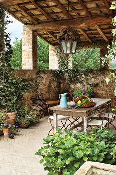 Terra-cotta pots fill a covered loggia.- HarpersBAZAAR.com