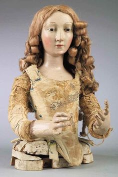 Polychromed Wood Mannequin Head and Torso ,18th c.,the female form with glass eyes and long blonde curled tresses, wearing antique stomacher, height 12 in., width 8 in., depth 8 in