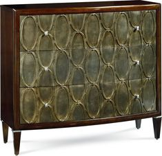 Spellbound Hall Chest  A raised oval pattern in hues of silver leaf and burnished bronze repeat across the chest's three drawer fronts. Modest hardware that all but disappears creates a trompe l'oeil effect. Framed in mahogany veneers and set on tapered legs with subtle polished nickel collars.
