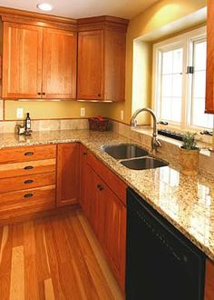 Smooth granite counters, a high-arc faucet, undermount stainless steel sink and black dishwasher show off this kitchen's modern appeal.