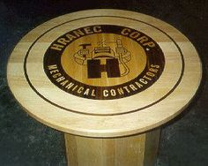 Specialty Woods custom built this solid maple round table with the corporate inlaid logo, by Neal Burns owner of Specialty Woods.