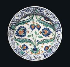 AN IZNIK POTTERY DISH -  OTTOMAN TURKEY, CIRCA 1580 -  With sloping rim on short foot, the white interior decorated in cobalt-blue, green, black & bole-red, with two recurved large green saz leaves issuing from a central tuft forming a broad cartouche enclosing two bold palmettes in blue & red, the interstices filled with smaller palmettes, the rim with stylized wave and rock motif in blue & black, the edges painted to imitate cusping, with alternating paired tulips  11 5/8in.  diam.