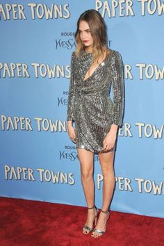 "For the New York ""Paper Towns"" premiere, Delevingne wore a pair of strappy metallic heels and a silver Saint Laurent dress and Alejandra G heels."